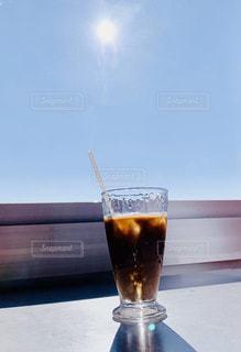カフェ,風景,空,コーヒー,太陽,アイスコーヒー,晴れ,青空,晴天,青,黒,水滴,影,氷,ガラス,光,テーブル,ストロー,グラス,喫茶店,窓際,ドリンク,飲料,ソフトド リンク