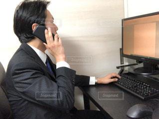携帯電話で話しているラップトップコンピュータを使っている男の写真・画像素材[3066508]