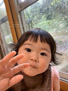 窓の前に座っている小さな女の子の写真・画像素材[2803313]
