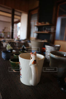 レトロな木目のテーブルに置かれたマグカップの写真・画像素材[2894437]