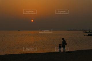 真っ赤な夕日と親子のシルエットの写真・画像素材[2898137]