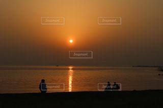 夕日を見ながら黄昏れる人々の写真・画像素材[2898139]