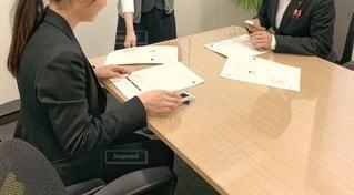 机に座っている人の写真・画像素材[2878467]