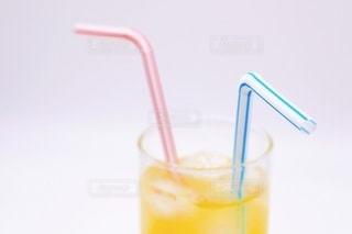 オレンジジュースとストローの写真・画像素材[3491184]