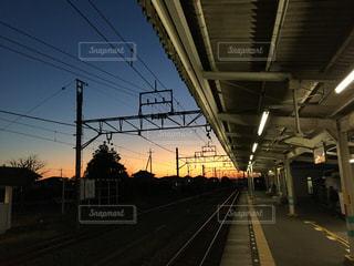 空,太陽,駅,電車,晴れ,青空,晴天,線路,光,朝焼け,地平線,日の出,鉄道,ホーム,マジックアワー,駅舎,架線