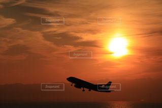 夕暮れの空を飛ぶ飛行機の写真・画像素材[2880754]