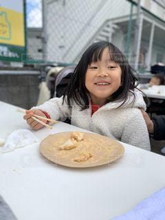 食べ物を食べるテーブルに座っている小さな女の子の写真・画像素材[2920916]