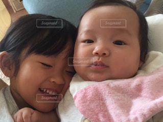 赤ん坊を抱いている小さな女の子の写真・画像素材[2920925]