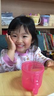 テーブルの上に座っている小さな女の子の写真・画像素材[2920929]