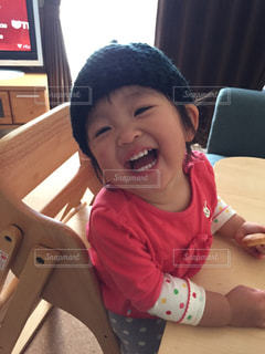 テーブルの上に座っている小さな子供の写真・画像素材[2920934]