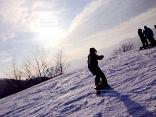雪に覆われた斜面をスノーボードに乗っている男の写真・画像素材[2955618]
