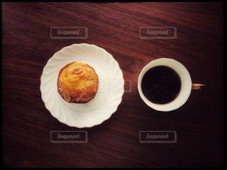 木製のテーブルの上に座っているマフィンとコーヒーのカップの写真・画像素材[2921965]