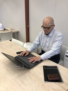 ノートパソコンを使ってテーブルに座っている男性の写真・画像素材[2879559]