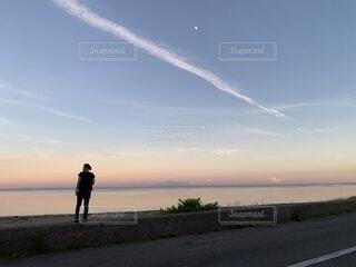 夕焼け空を前に佇む人の写真・画像素材[4664959]