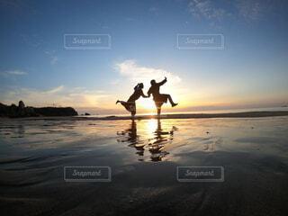 夕日を前にはしゃぐカップルの写真・画像素材[4665005]