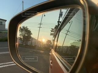 車のミラー越しに見た夕日の写真・画像素材[4737541]