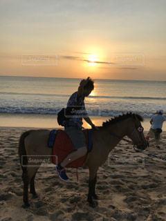 ビーチで馬に乗っている人の写真・画像素材[2899846]