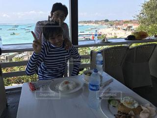 食べ物を食べるテーブルに座っている人の写真・画像素材[2914423]