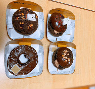 木のテーブルの上に座っているドーナツで満たされた箱の写真・画像素材[2958926]