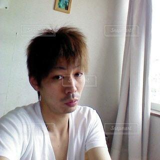 窓の前に座っている若者の写真・画像素材[3365735]