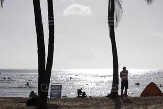 水域の近くのビーチで数人の人々の写真・画像素材[2906648]