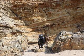 男性,子ども,友だち,3人,自然,海,屋外,砂浜,山,景色,岩,地面,洞窟,石,ハイキング,峡谷