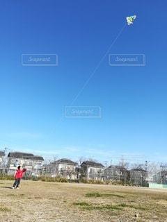 晴れた日に凧を飛ばす少年の写真・画像素材[2981913]