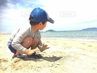 砂浜の上に座っている小さな男の子の写真・画像素材[2981957]
