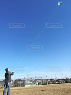 晴れた日に凧を飛ばす男の写真・画像素材[2987380]