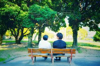 公園のベンチに座っている二人の写真・画像素材[3029899]