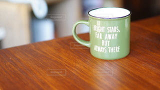 木製のテーブルの上に座っているコーヒーのカップの写真・画像素材[2925510]