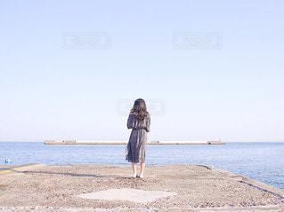 水域の近くのビーチに立っている人の写真・画像素材[3553954]