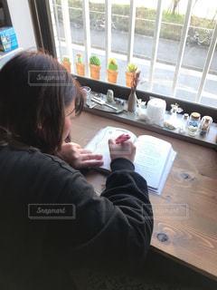 窓の前のテーブルに座っている人の写真・画像素材[3026218]
