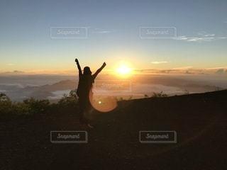 夕日の前に立っている人の写真・画像素材[3576031]