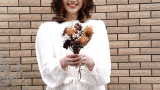 笑顔でドライフラワーを胸の前で持つ女性の写真・画像素材[4230771]