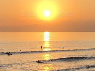 サーファーと夕陽に染まる海岸の写真・画像素材[3344604]