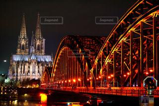 ケルン大聖堂を背景に夜にライトアップされた大きな橋の写真・画像素材[3002981]