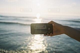 自然,海,空,夏,屋外,ビーチ,手,水面,夕方,スマホ,手持ち,人物,iphone,ポートレート,ライフスタイル,手元,日中,電子機器