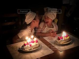 キャンドルとバースデー ケーキの前に座っている双子の写真・画像素材[1683378]