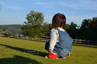 子ども,芝生,屋外,後ろ姿,女の子,背中,後姿,しゃがむ,グリーン,オーバーオール,伸びた影