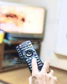 男性,1人,リビング,屋内,黒,手,指,リラックス,人,テレビ,ボタン,休日,暇,TV,自宅,休暇,リモコン,チャンネル,ゆび