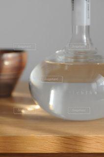 木製テーブルの上に座っている花瓶の写真・画像素材[1261736]