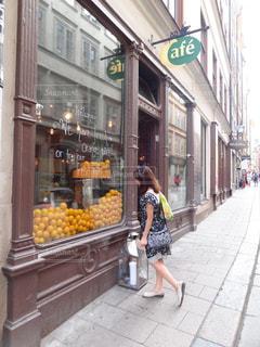 女性,建物,街角,スウェーデン,海外,散歩,オレンジ,石畳,道,フルーツショップ,おしゃれな街