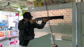 ゲームセンターのクレー射撃をガチでプレイする男性の写真・画像素材[3032816]