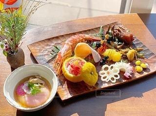 木のお皿にのっかってるおせち料理の写真・画像素材[4046320]