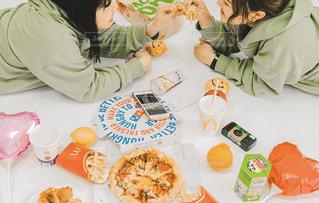食べ物の皿を持ってテーブルに座っている女性の写真・画像素材[3066974]