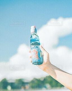 空,夏,屋外,手,指,手持ち,人物,人,キラキラ,ボトル,ポートレート,ドリンク,ラムネ,ライフスタイル,手元,物,持つ,ソフトド リンク