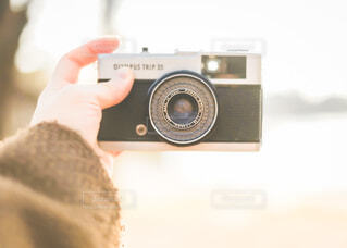 カメラ,手,指,手持ち,人物,人,キラキラ,デジタルカメラ,レンズ,ポートレート,ライフスタイル,フィルムカメラ,手元,一眼レフカメラ,物,持つ,ミラーレス一眼カメラ,コンパクトカメラ,エレクトロニクス,カメラレンズ,レフレックスカメラ,カメラ光学