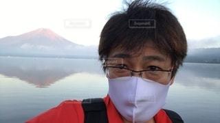 眼鏡をかけてマスクをしてカメラを見ている人のクローズアップの写真・画像素材[3567503]