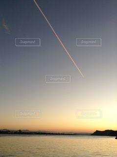 海と夕暮れと飛行機雲の写真・画像素材[3394397]